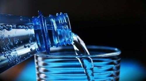 häller vatten i glas