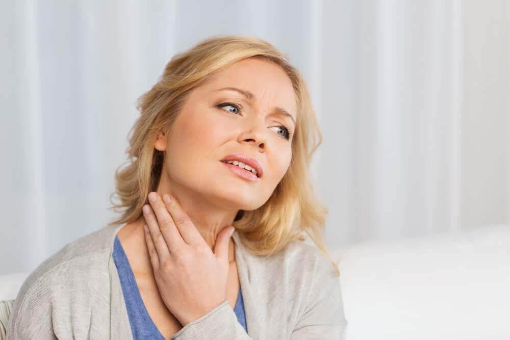 kvinna undersöker sin hals efter knutor på sköldkörteln