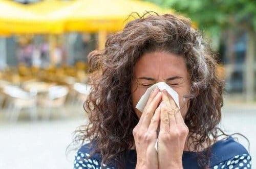 kvinna nyser i näsduk på grund av höga inomhustemperaturer
