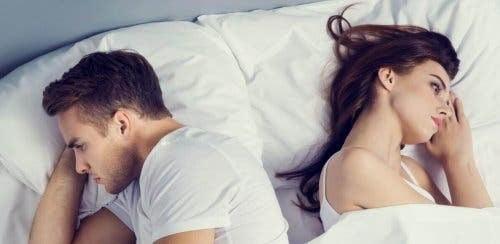 par ligger med ryggarna mot varandra i säng