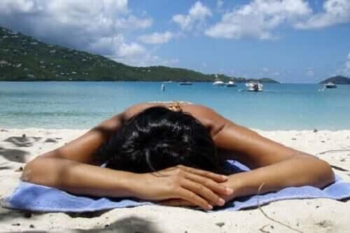 kvinna solar och kommer att uppleva effekterna som värme kan ha på kroppen