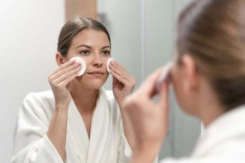 En kvinna framför spegeln sminkar sig med produkter med a-vitamin.