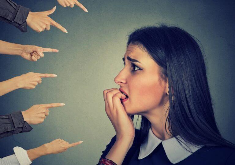 Fingrar pekar på en rädd kvinna som biter på naglarna.