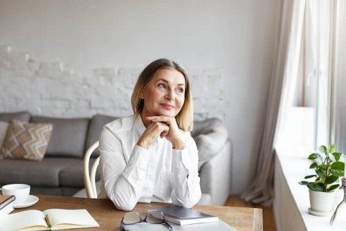 Nöjd kvinna sitter vid skrivbordet och tänker.