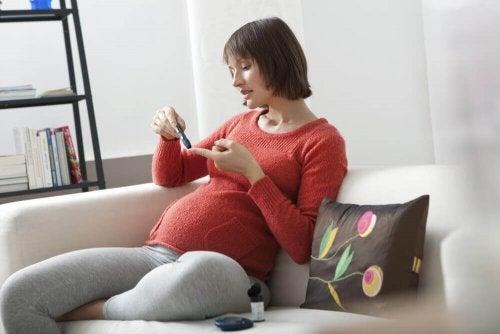 Gravid kvinna sticker sig i fingret för att kolla blodsockernivåerna.