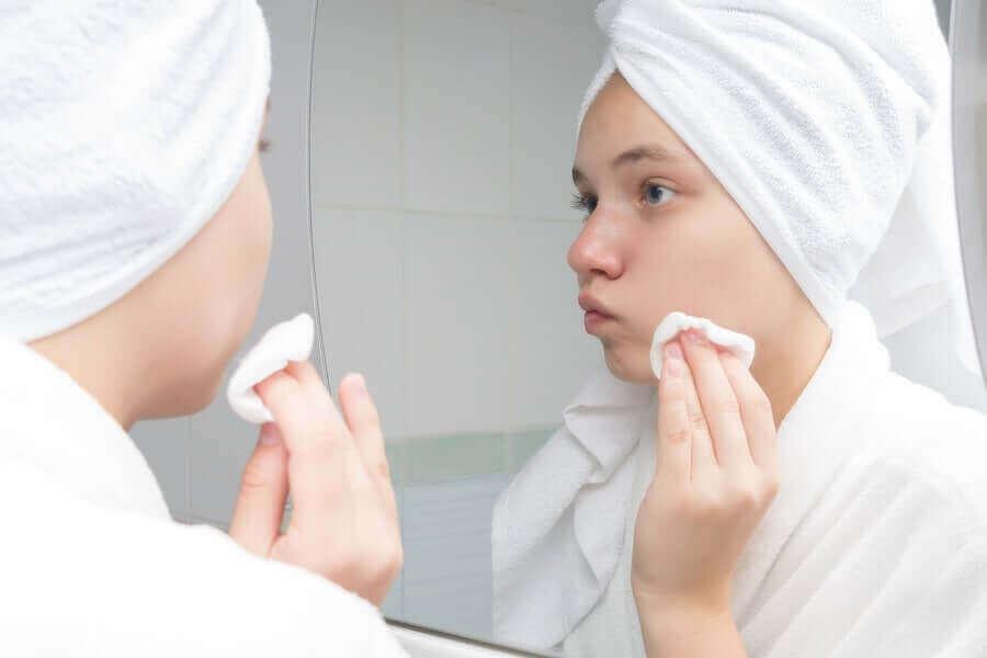 Kvinna behandlar akne med medel på bomullstuss.