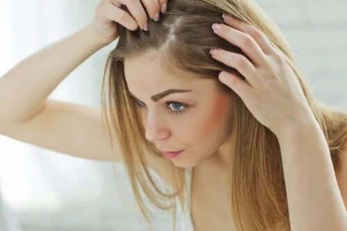Kvinna letar efter grå hårstrån.