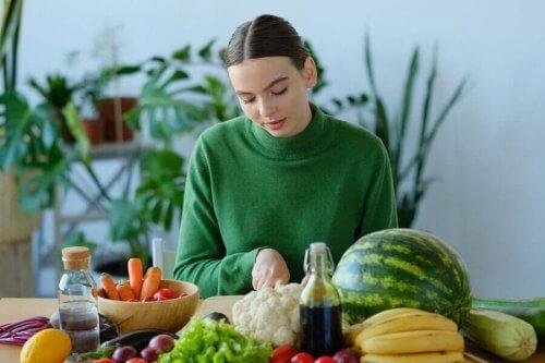 En kvinna omgiven av frukt och grönsaker fulla med A-vitamin.