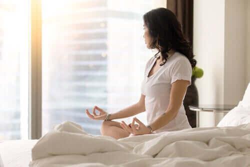 Kvinna sitter på sängen och mediterar.