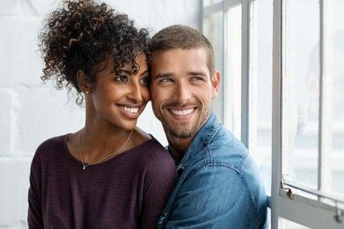 Ett lyckligt par tittar ut genom fönstret.