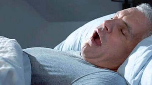 Man sover och snarkar med öppen mun.