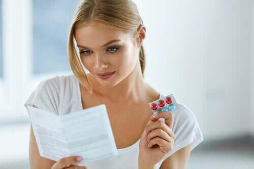 Kvinna håller medicin och en bipacksedel i handen.