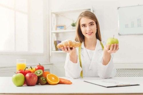 Nutritionist håller i ett äpple och en croissant.