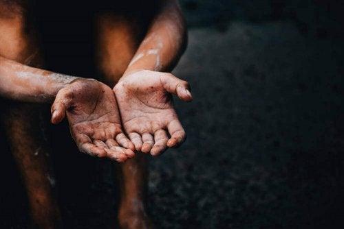 En person håller fram sina smutsiga händer.