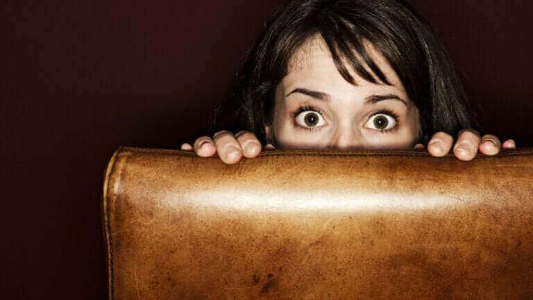 En rädd kvinna gömmer sig bakom en stol.