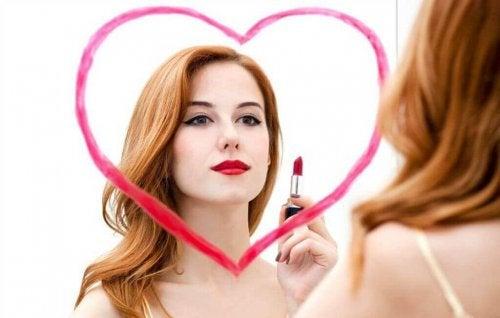 Kvinna ser sitt vackra jag i spegeln.