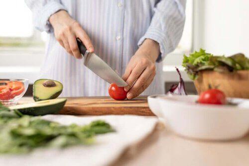 Person står i köket och skär grönsaker till en sallad.