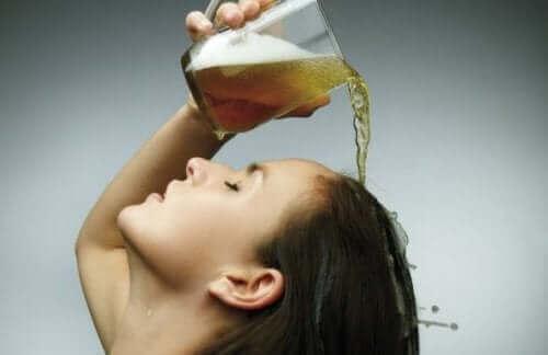 Kvinna sköljer håret med öl.
