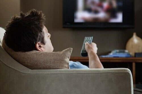 Man sitter i soffan och slötittar på TV.