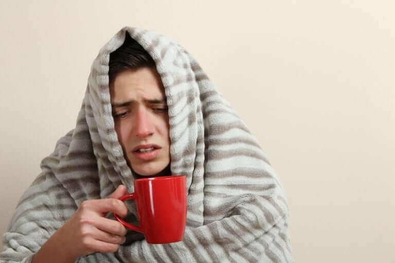 En man dricker te för att lindra symtom.