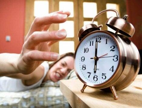 Kvinna stänger argt av sin väckarklocka på morgonen.