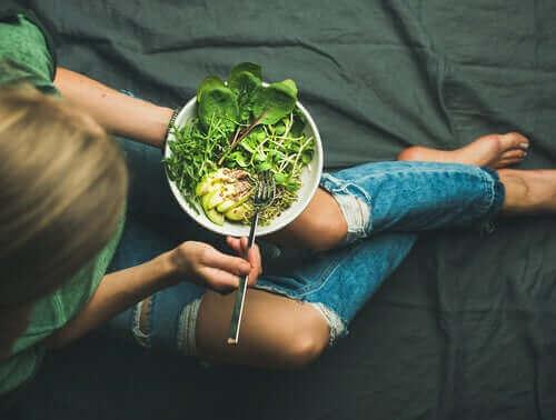 En kvinna äter en nyttig sallad.