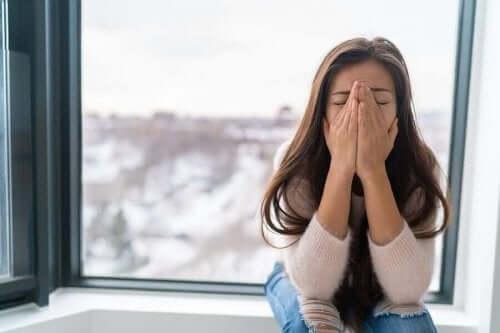 Kvinna sitter framför ett fönster och gråter.