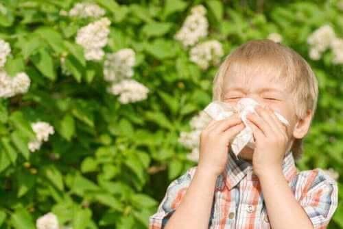 En pojke som har barnastma och nyser i en näsduk.