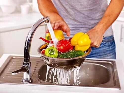 frukt med skal: kvinna sköljer grönsaker