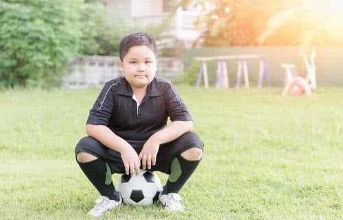 Fysisk inaktivitet hos barn: pojke sitter på fotboll