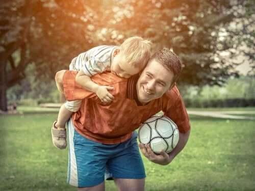 Far och son tar en paus i fotbollsspelande.