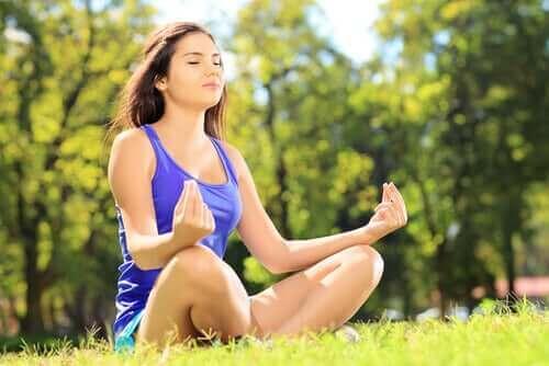 Kvinna sitter utomhus och mediterar.