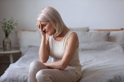 symptomen på perimenopaus: kvinna sitter på säng och ser trött ut