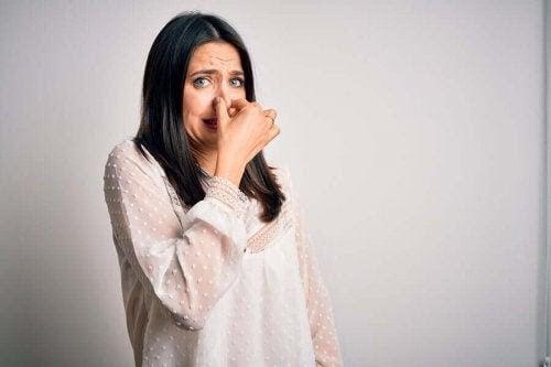 dermatitis neglecta: kvinna håller för näsan