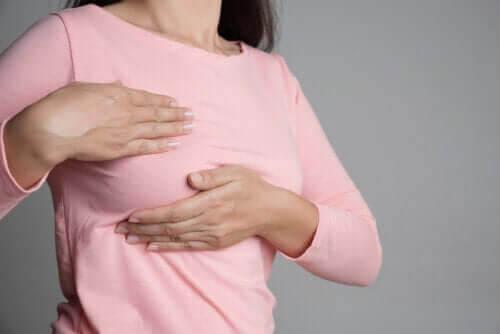 bröstsmärtor och menstruationscykeln: kvinna känner på sitt bröst
