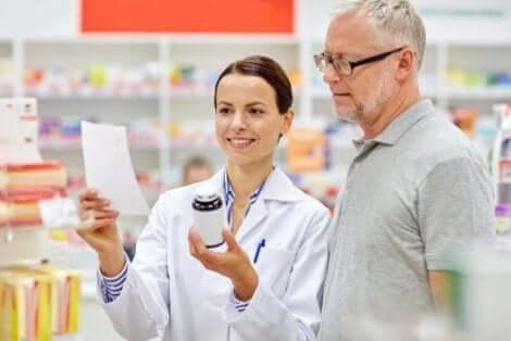 En farmaceut visar vad bipacksedeln innehåller för en kund.
