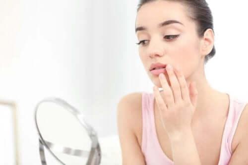 Hur behandlar man munsår: En kvinna tittar sig i spegeln.