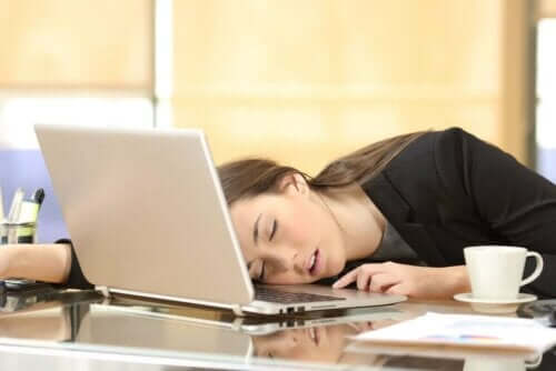 En kvinna sover vid datorn.
