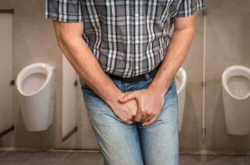 Man med urinvägsinfektion håller sig för skrevet.