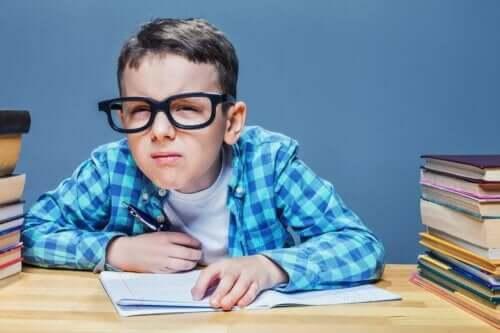 Pojke med glasögon kisar när han läser.
