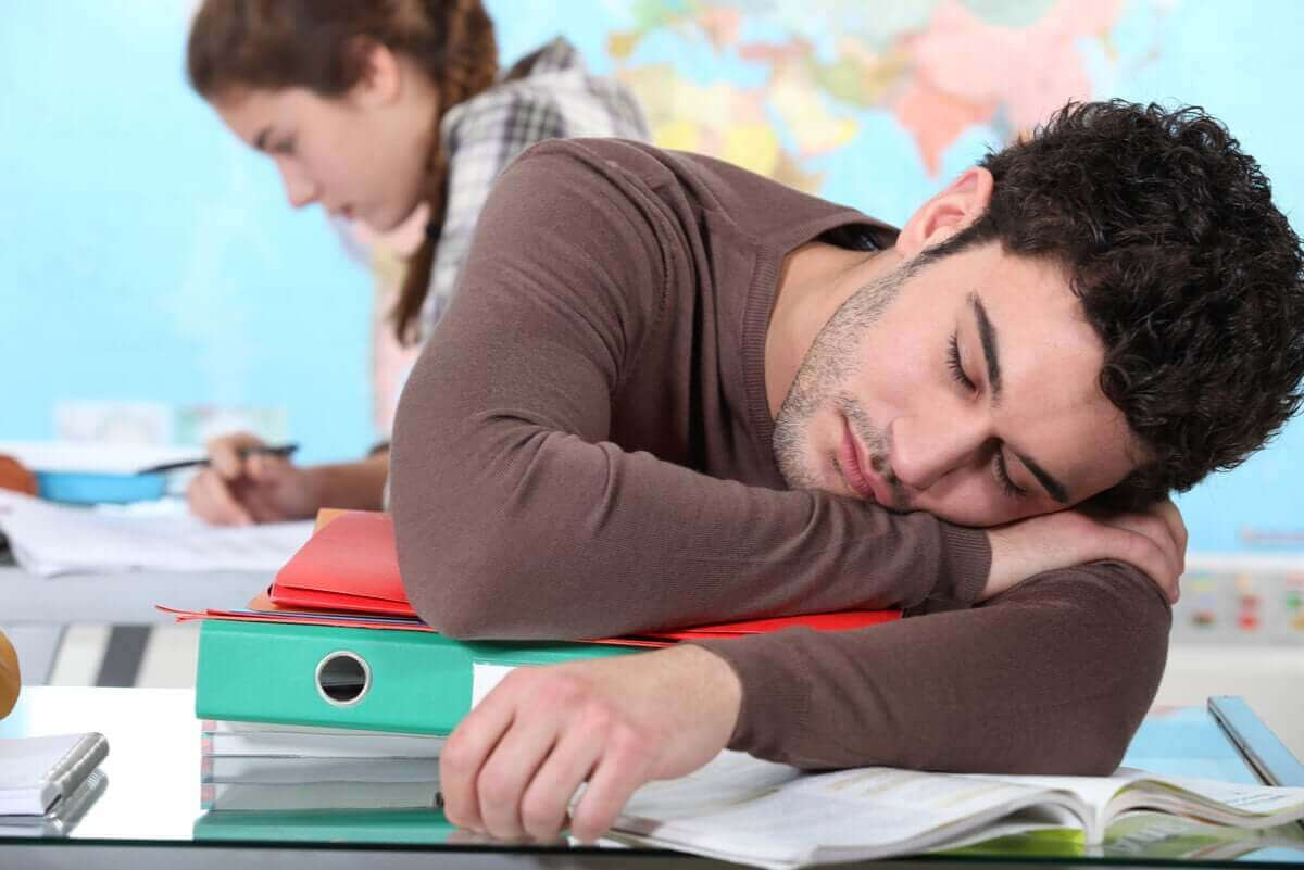 En student har somnat på sina böcker.