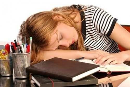 Högt ferritinvärde: En trött kvinna som somnat över sina böcker.