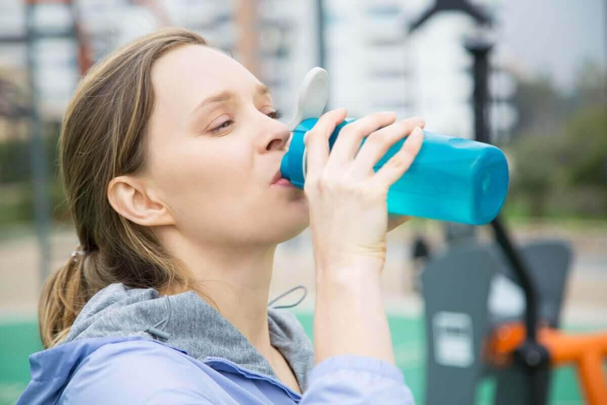 kvinna dricker vatten för att upprätthålla vätske- och elektrolytbalansen
