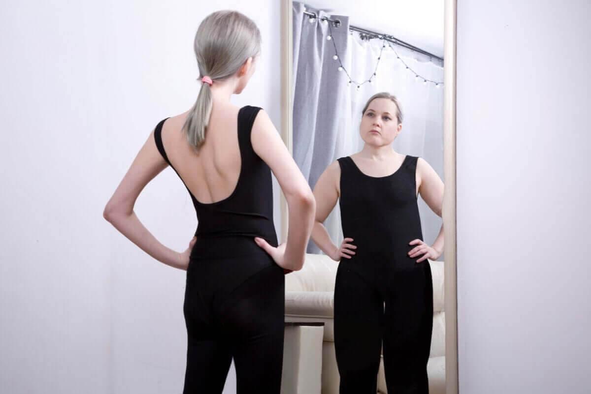 ätstörningen sadorexi: smal kvinna ser sig själv som tjock i spegel