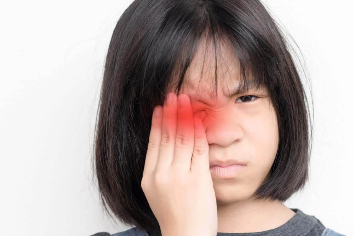 Förändringar i ögonfärgen: flicka med ont i ögat