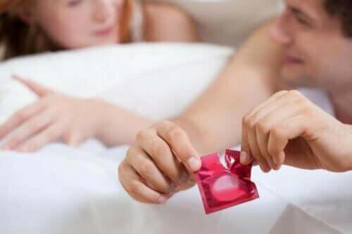 Samband mellan preventivmedel och blodpropp: En man öppnar en kondom.