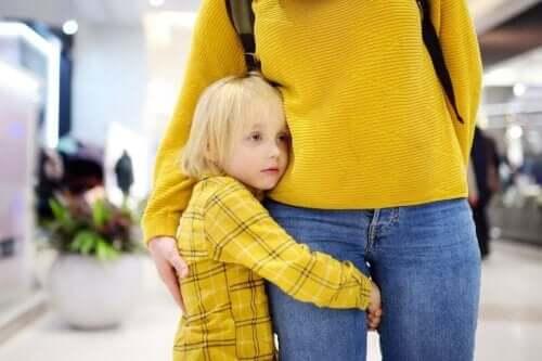 Barn kramar om sin mammas ben.