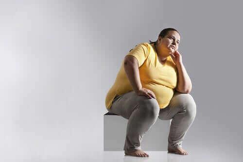 Fet kvinna sitter ner på en låda.