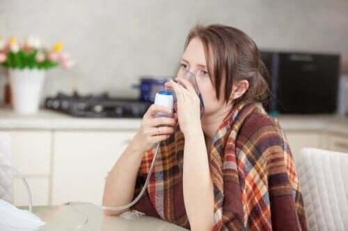 Kvinna använder inhalator för tung andning.