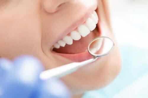 Tandläkare tittar på en persons tänder.
